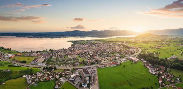 Luftaufnahme mit Drohne für ein Immobilienprojekt in Lachen/Schwyz mit Sonnenaufgang und Sicht auf den Obersee und Säntis