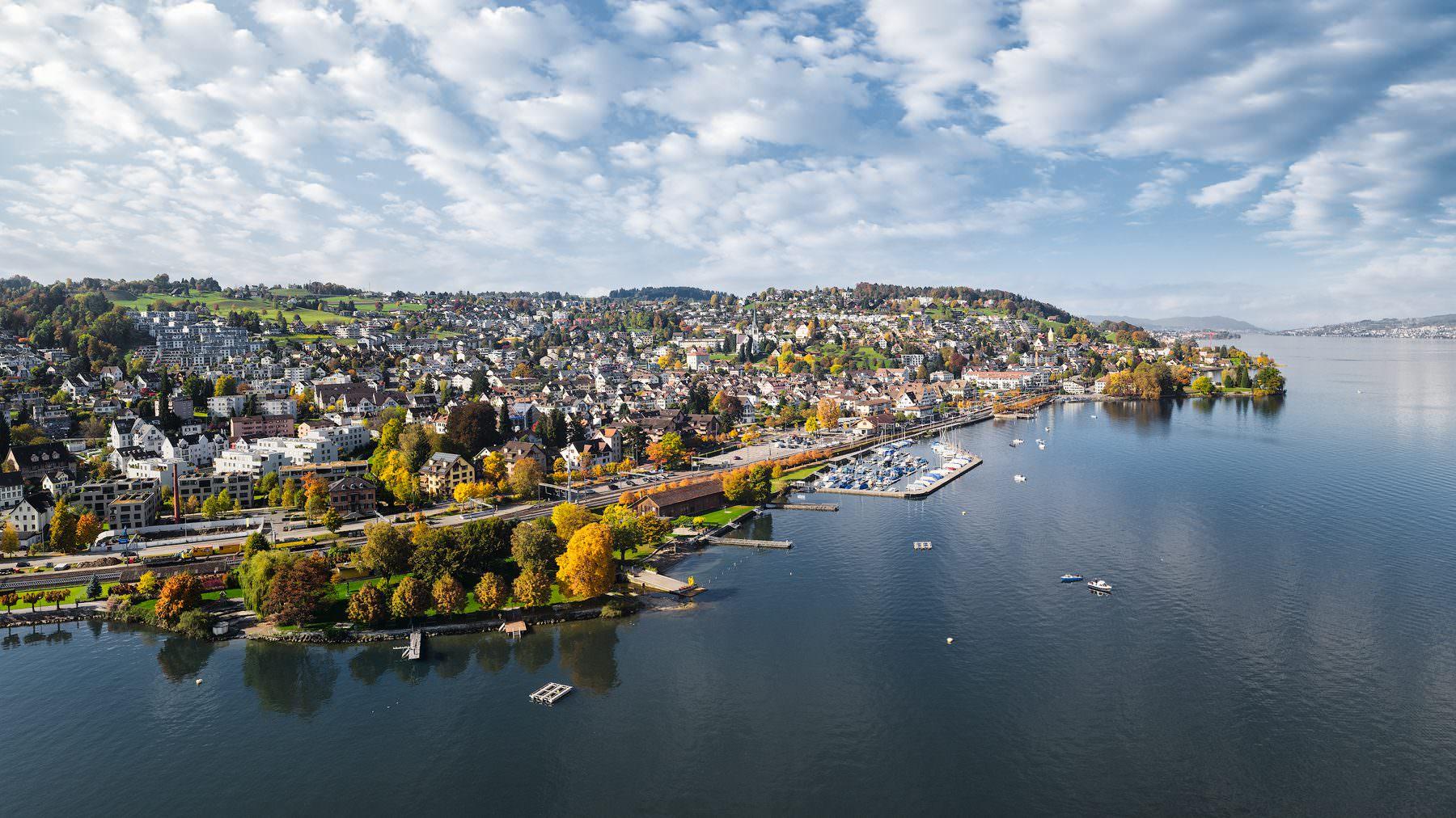 Herbstliche Luftaufnahme mit Drohne hoch über dem Zürichsee mit Blick auf Richterswil, Seebad, Hafen, Bahnhof, Horn, Uetliberg und Zürich © by Gerry Pacher © by Gerry Pacher