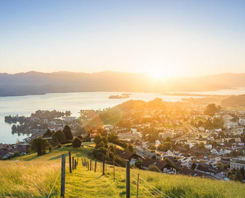 Sonnenaufgang über Wollerau mit Blick auf den Zürichsee, die Inseln Ufenau und Lützelau, dem Damm, Rapperswil, Säntis