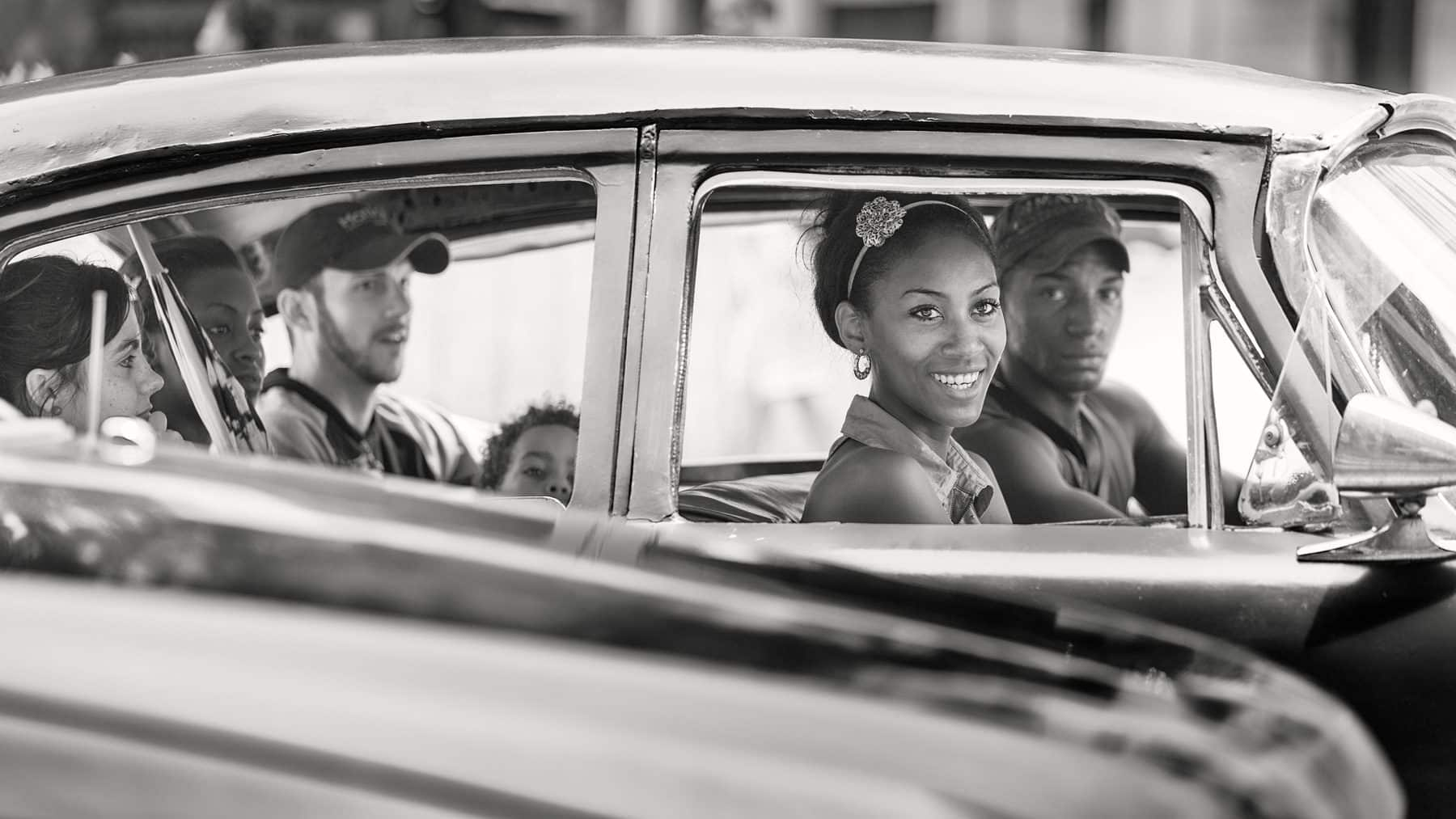 Cuba Havanna Monte Street.Traffic jam - a perfect moment to photography the various scenery. She smile to someone - i don't no who. But the driver and the little kid discoverd me … Copyright © by Gerry Pacher