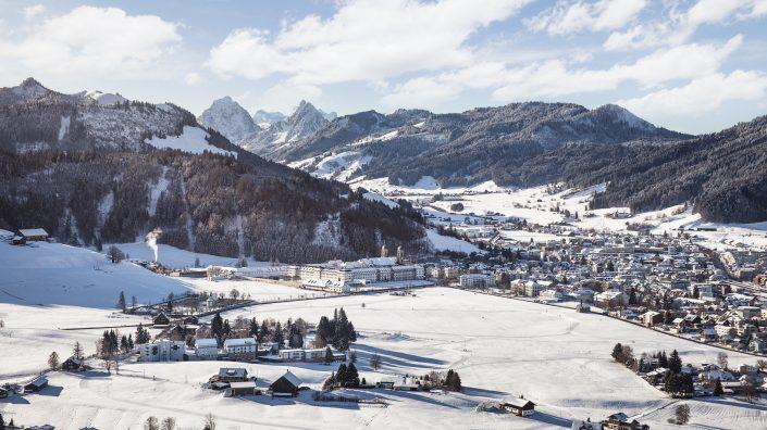 Luftaufnahme mit Helikopter winterliches Einsiedeln mit Hotel Allegro, Kloster, Grosser und Kleiner Mythen