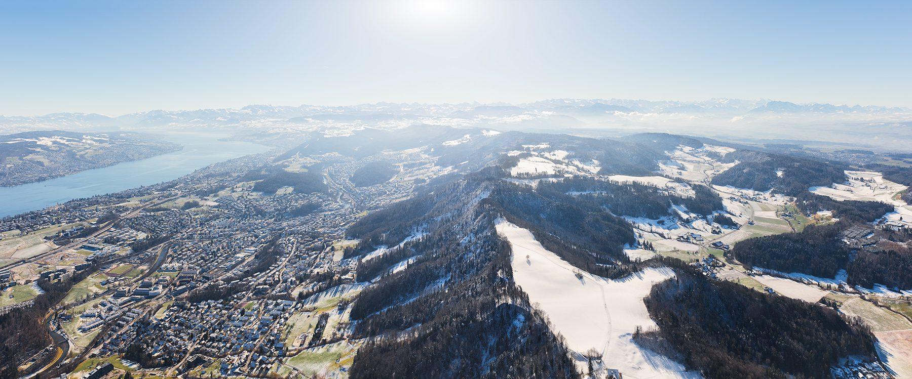 Winterliche Luftaufnahme mit Helikopter hoch über Adliswil mit Sicht auf den Zürichsee, Horgen, Wädenswil, Schwyz, Glarneralpen, Kanton Zug, Innerschwyz