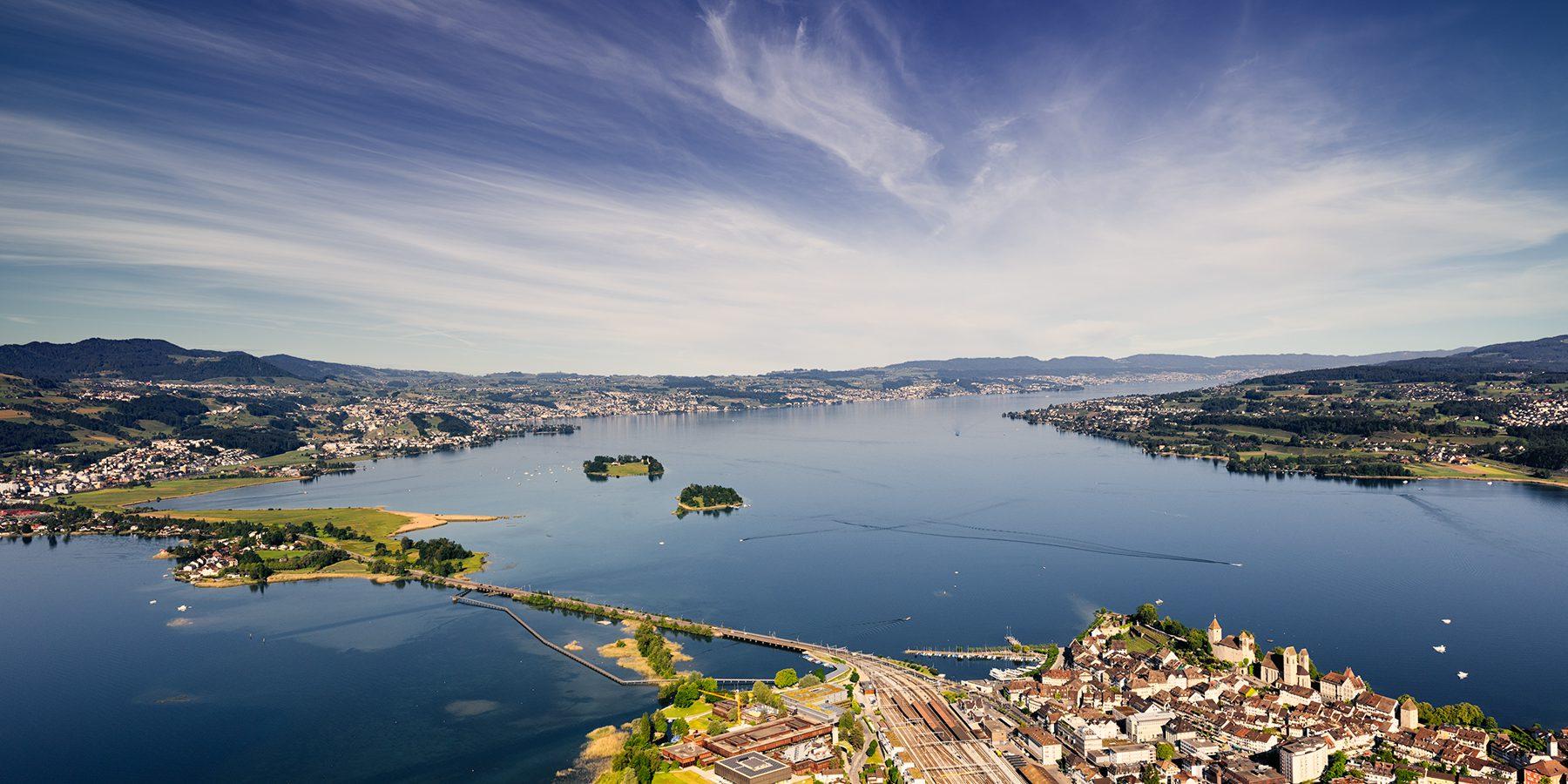 Luftaufnahme mit Helikopter hoch über Rapperswil mit Blick auf Damm, Obersee, Zürichsee, Ufenau und Lützelau