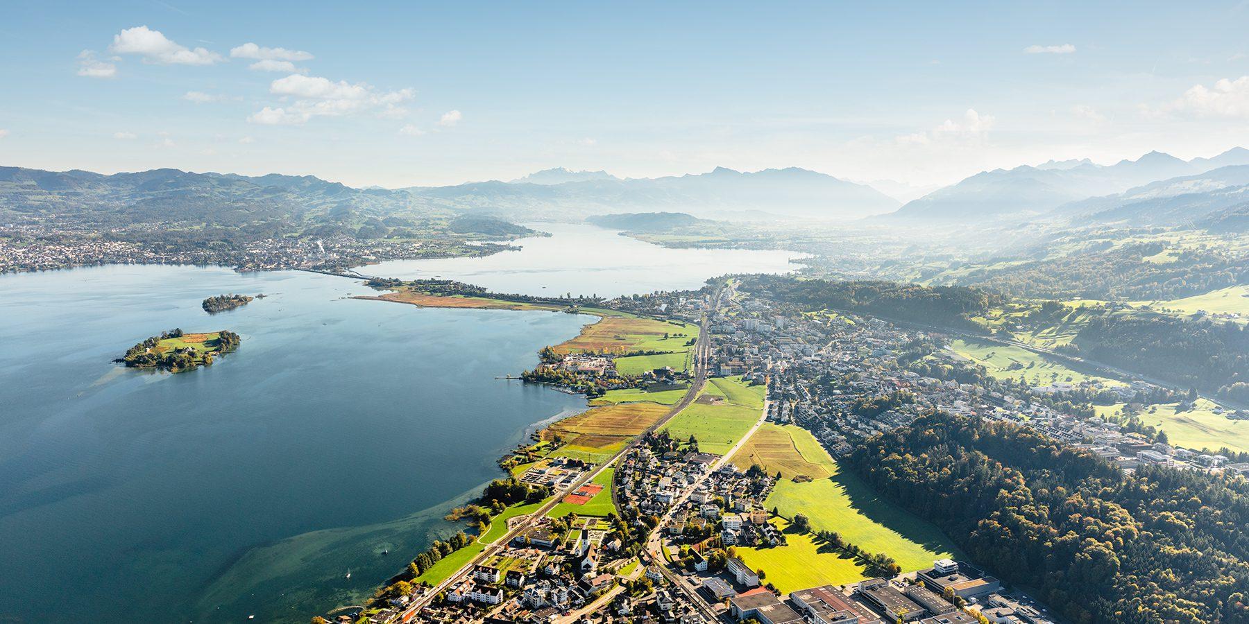 Luftaufnahme mit Helikopter hoch über Wilen bei Wollerau mit Blick auf den Zürichsee, Obersee, Ufenau, Lützelau, Pfäffikon, Hurden, Damm, Rapperswil, Jona, Altendorf, Lachen, Linthebene, Speer, Federispitz, Säntis
