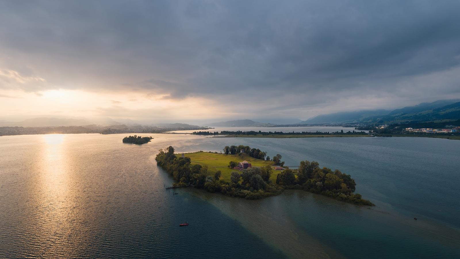 Luftaufnahme eines sommerlichen Sonnenaufgangs hoch über dem Zürichsee mit Blick auf Ufenau, Lützelau, Pfäffikon, Damm, Obrersee, Rapperswil