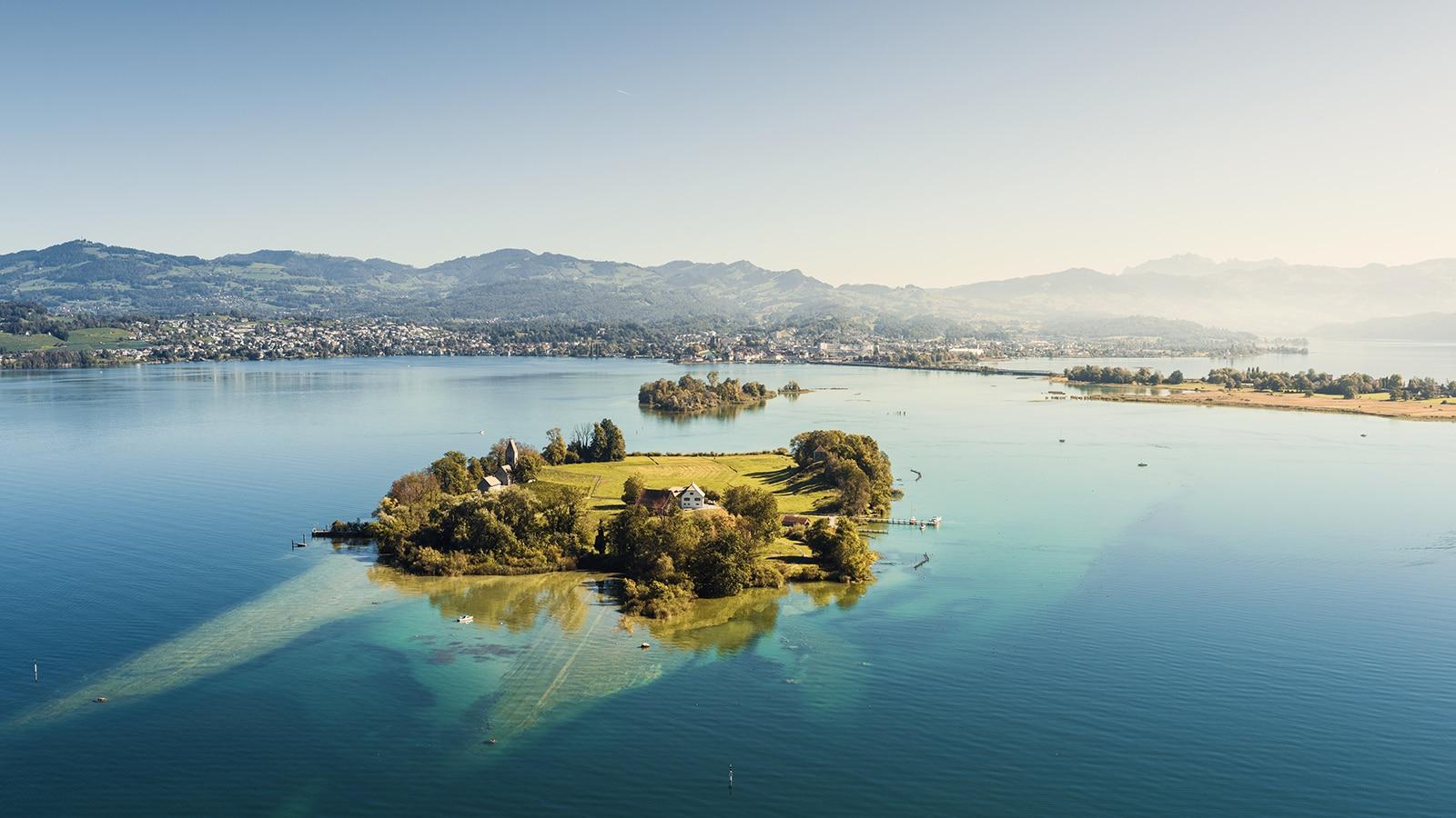 Luftaufnahme mit Helikopter über dem Zürichsee mit Blick auf Ufenau, Lützelau, Damm, Rapperswil, Bachtel, Ricken, Obersee, Säntis