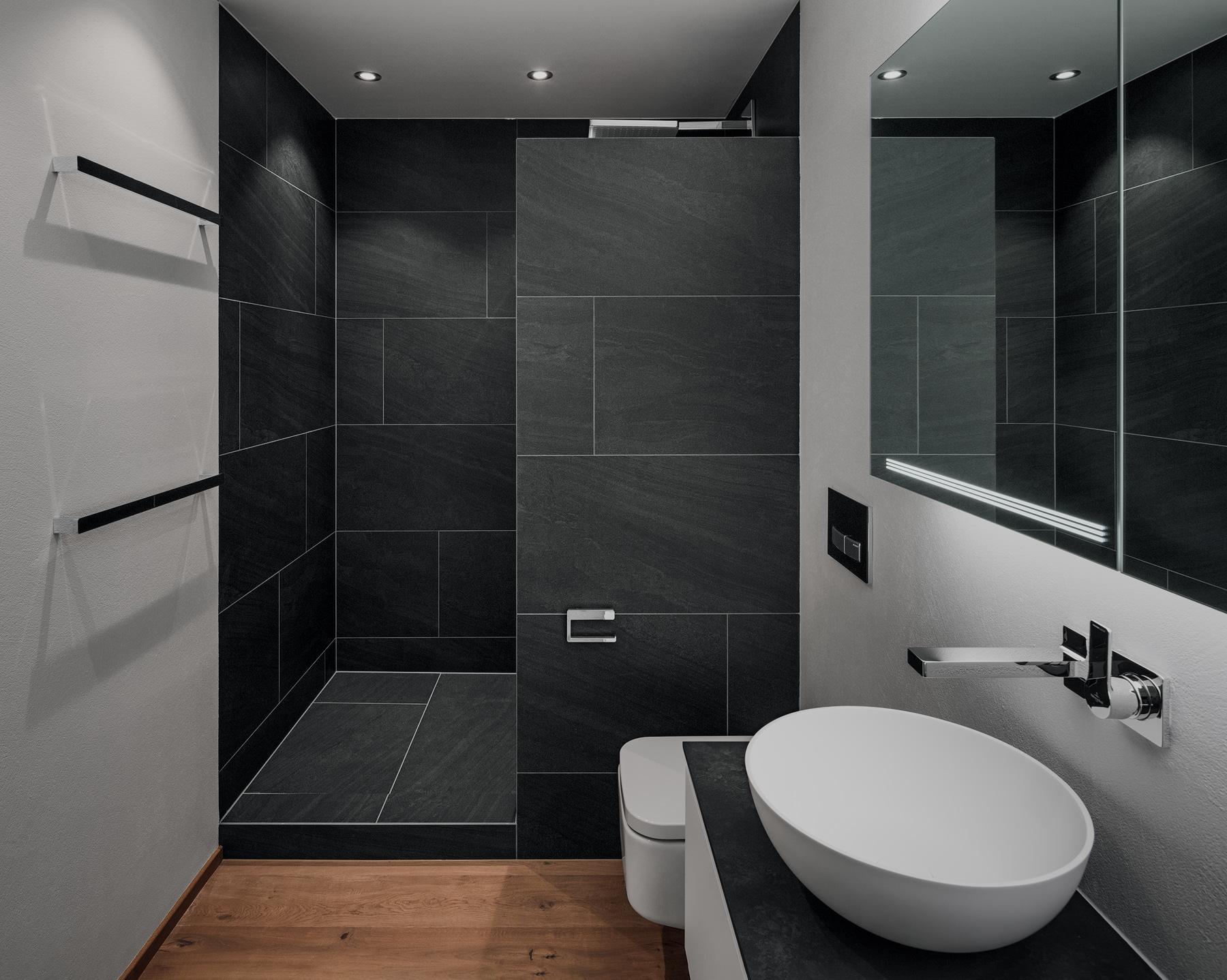 Weisses Bad mit. schwarzem Duschbereich und Holzboden