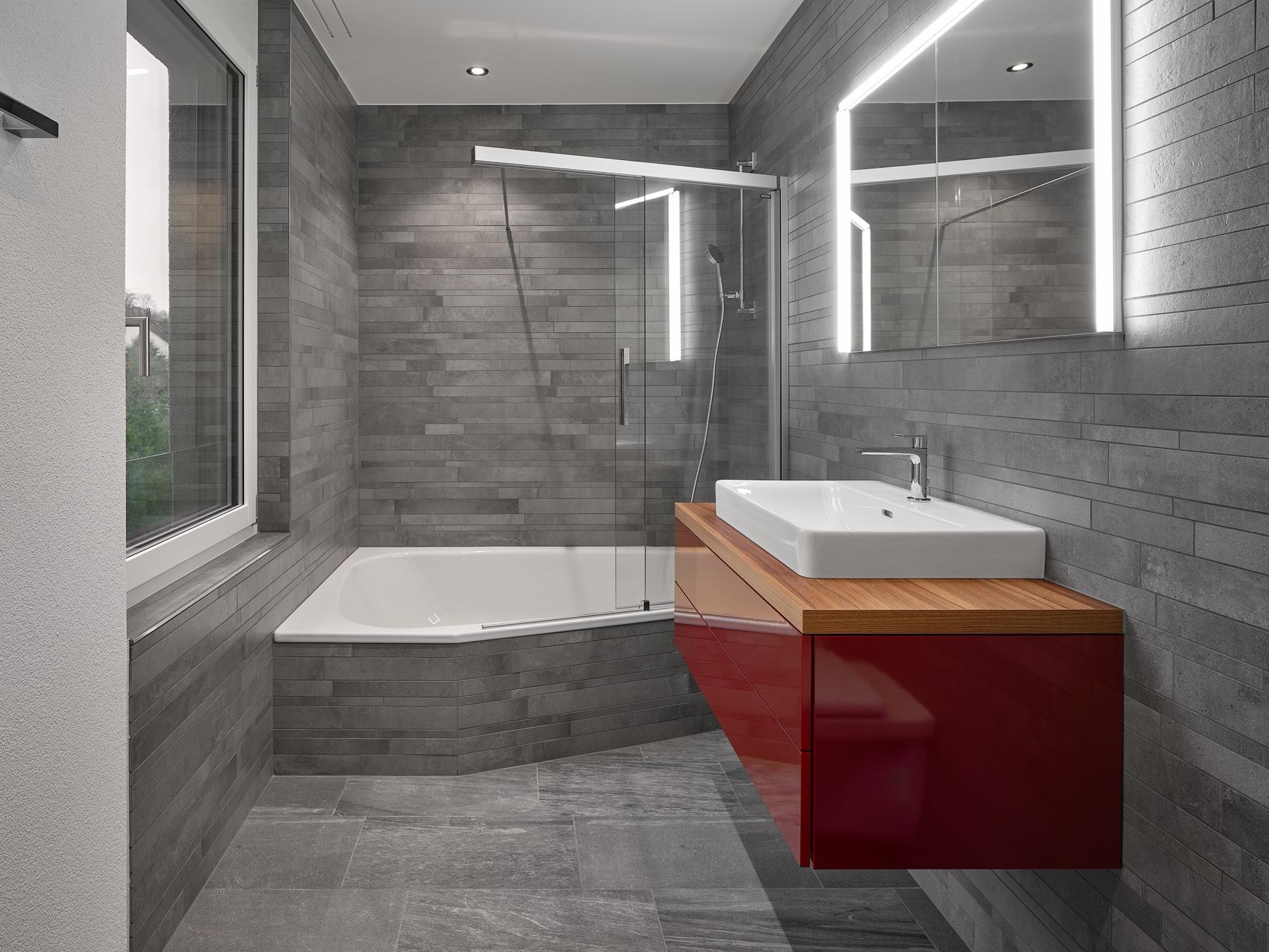Bad mit grauen Natursteinplatten, asymmetrischer Badewanne, rotem Badmöbel