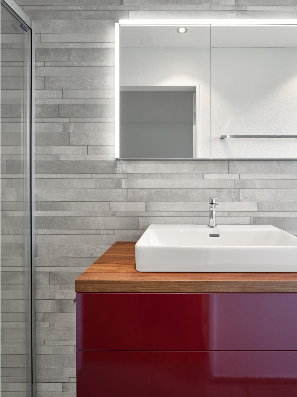 rotes Badmöbel mit weissem Lavabo und grauen Wandplatten