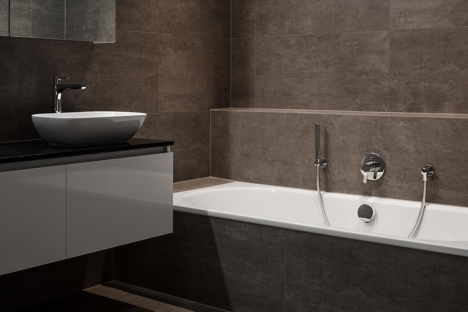 Braunes Bad mit Badewanne und weissem Badmöbel / Lavabo