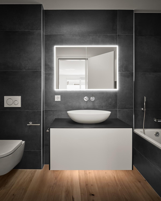 Schwarzes Bad mit Badewanne, Led-Spiegel, geöltem Holzboden