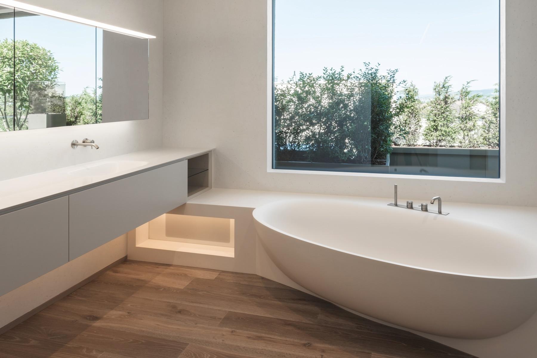 Cremefarbenes Stucco Veneziano Bad mit ovaler Badewanne und geöltem Holzboden