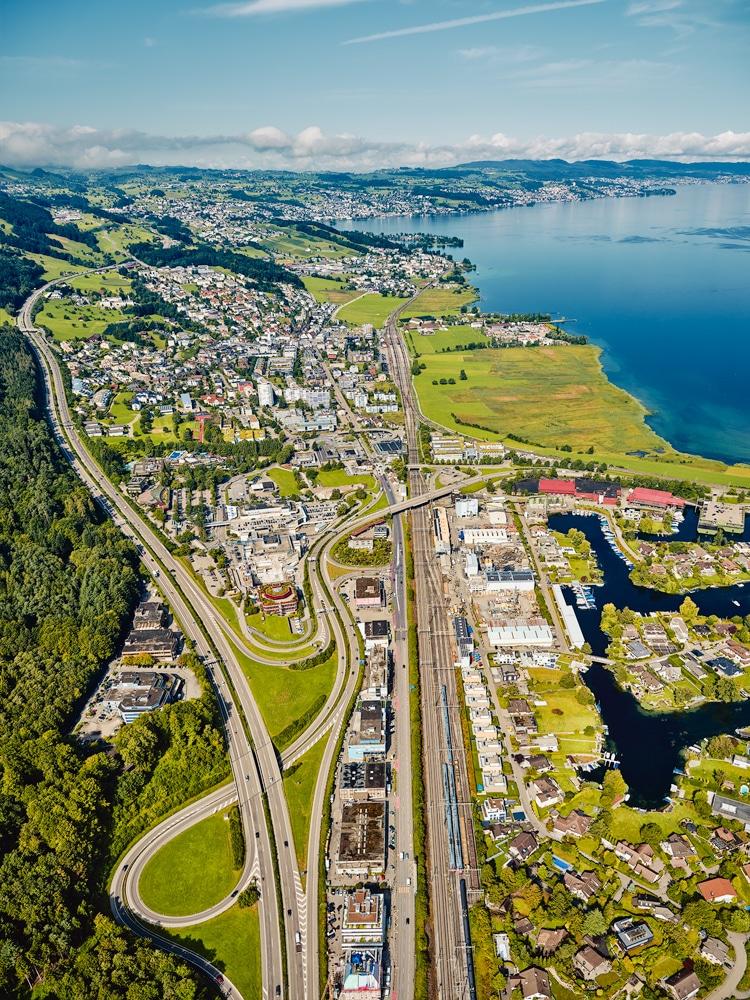 Luftaufnahme mit Helikopter hoch über Pfäffikon/SZ mit Blick auf die Autobahn, Eisenbahn, Seedamm Center, Hurden, Zürichsee, Freienbach, Wollerau
