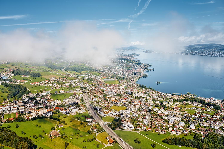 Luftaufnahme mit Helikopter hoch über Wollerau mit Blick auf die Autobahn, Wollerau, Richterswil, Wädenswil, Zürichsee und Zürich