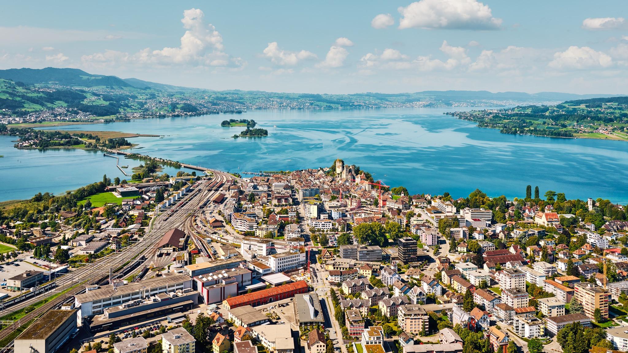 Luftaufnahme mit Helikopter hoch über Rapperswil mit Blick auf das Zentrum, dem Schloss, Hafen, Bahnhof, Damm Hurden, Obersee, Zürichsee