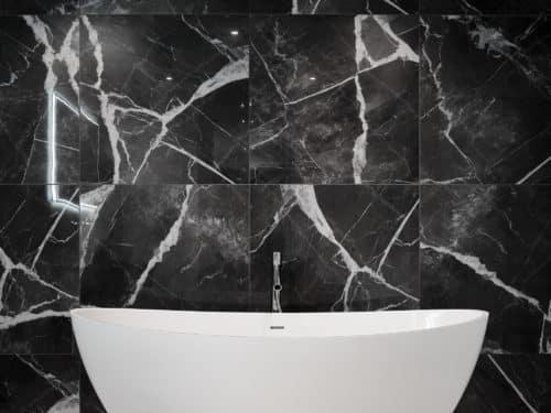 Freistehende Hoesch Glossy Badewanne mit hansgrohe Axor Starck Mischer und dunkler Marmorwand